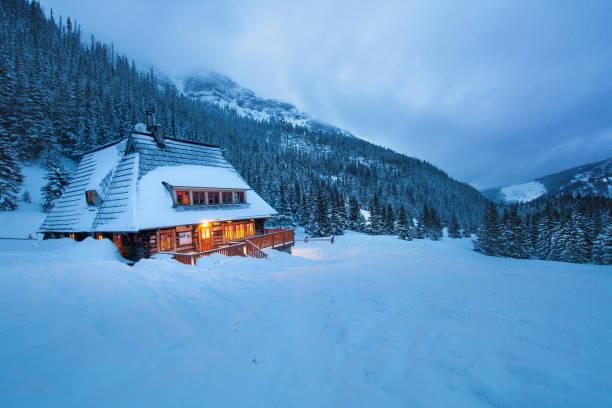 Une grande maison en bois dans les montagnes, à la tombée de la nuit