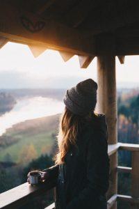 Jeune femme avec un bonnet, de dos, en train d'admirer la vue depuis le balcon d'un chalet en bois
