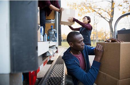 personnes chargeant des cartons dans un camion de déménagement
